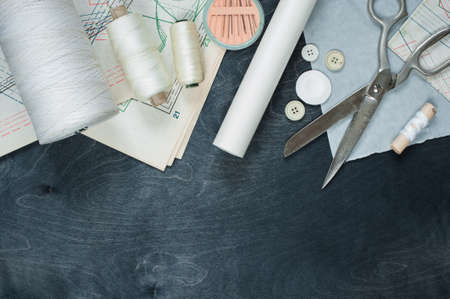 sewing pattern: Tools for sewing on the dark wooden background