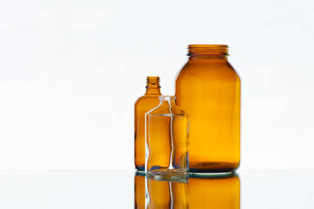 Empty various medicine bottles on the light background photo