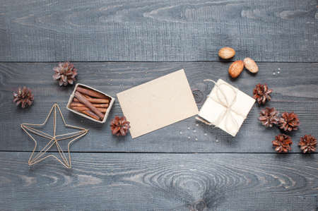 latter: Gift, card, pine cones, metal star and cinnamonin on the dark wooden textured table Stock Photo