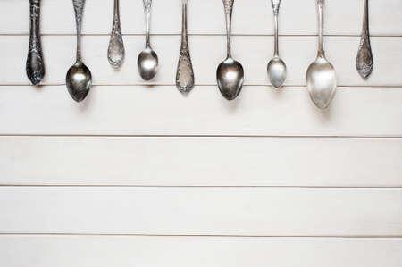 白いテーブルの上の銀スプーン 写真素材
