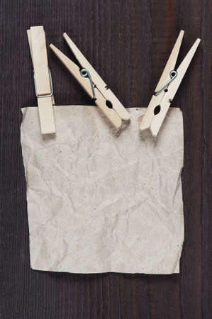 feuille froiss�e: Crumpled sheet of paper with clothespin on the dark wooden table