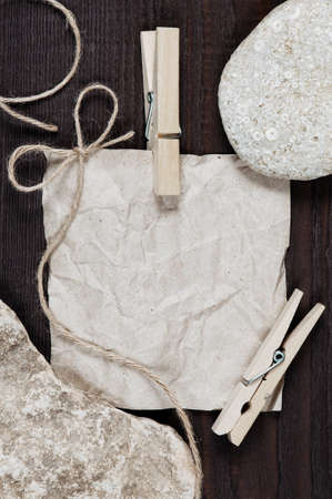 crumpled sheet: Empty crumpled sheet of paper, clothespin and bow on the dark wooden table