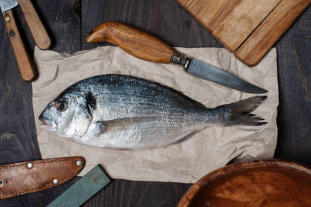 the dorada: Raw dorada on the wooden table with accesories