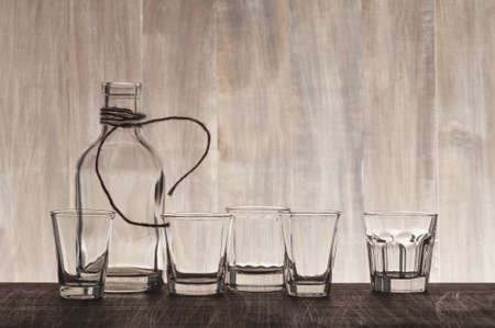 bar ware: Empty bottle and shots on the wooden bar counter