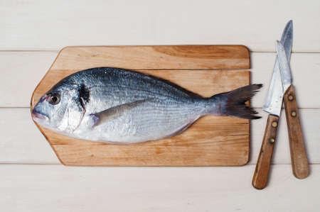 peces: Dorada cruda, tablero y cuchillos sobre la mesa de madera blanca Foto de archivo