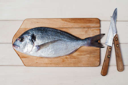 fish: Raw dorada, board and knifes on the white wooden table