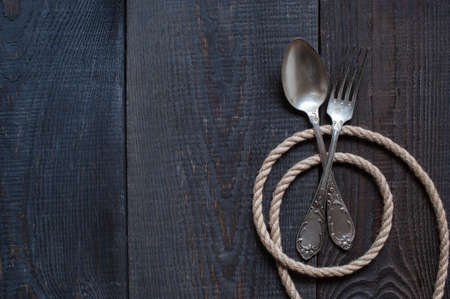 vintage cutlery: Vintage cutlery and rope on the old dark wooden table Stock Photo