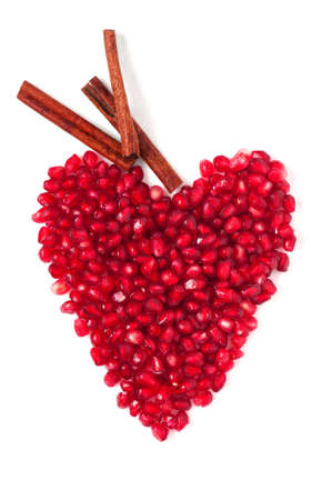 Red heart of pomegranate whith cinnamon on the light background