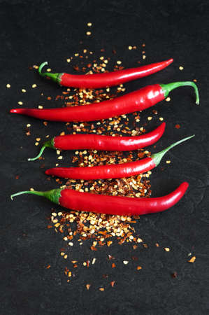crushed red peppers: Red hot chili peppers, whole and crushed on the black table Stock Photo