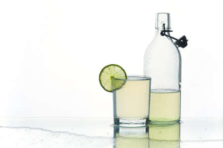 water spray: Glass and bottle with refreshment lemonade on the wet table on the white background Stock Photo