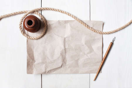 Empty crumple sheet of paper, inkpot, pen and rope on the white wooden table Stock Photo