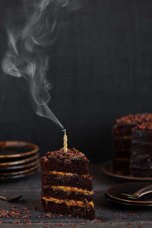 Piece of birthday chocolate cake with blown candle on the dark wooden table
