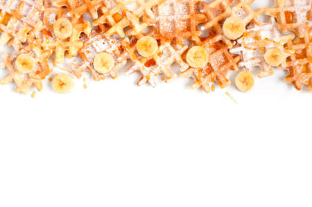 Background with many small waffles with banana and honey on the white table Stock Photo