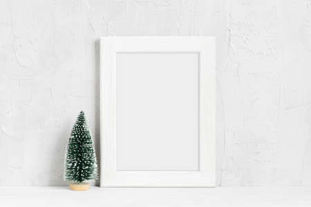 Minimalistic Cristmas mock-up with white wooden frame and small cristmas tree on the table