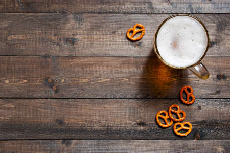 Wooden background with beer mug and salted pretzels, copy space