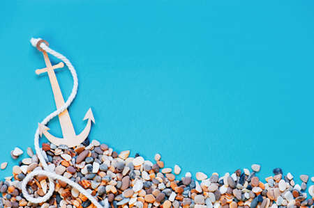 Blue background with handmade paper anchor on the pebble, copy space