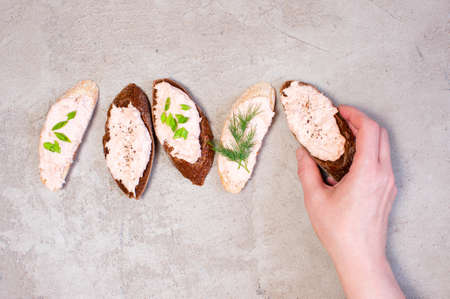 Female hand holding piece of rye bread with salmon pate, gray table