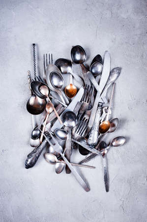 Vintage silverware scattered on the textured grey table, top view  Stock Photo