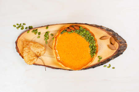 Fresh homemade pumpkin pie decorated with seeds and nuts on the white wooden table,  top view Stock Photo