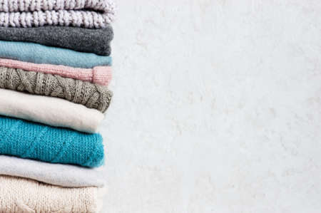 Light background with stack of knitted casual clothes various colors and textures, copy space