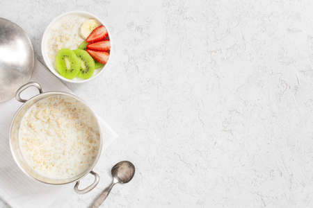 Background with oatmeal porridge and fresh fruits on the white table, healthy and nutritious breakfast, top view
