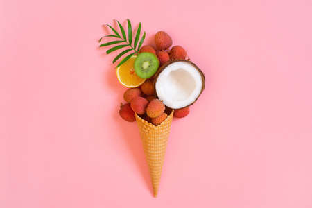 Concept of tropical ice cream with coconut and palm leaf, top view