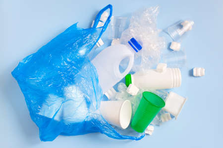Various plastic garbage on the light blue background, problem of waste sorting and utilisation