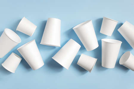 Various white disposable cups on the light blue background, top view