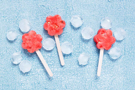 Popslices of fresh watermelon and ice on the blue background, top view Imagens