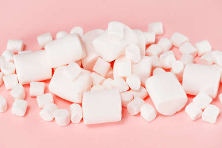 Various white marshmallows on the pink background, pastel composition