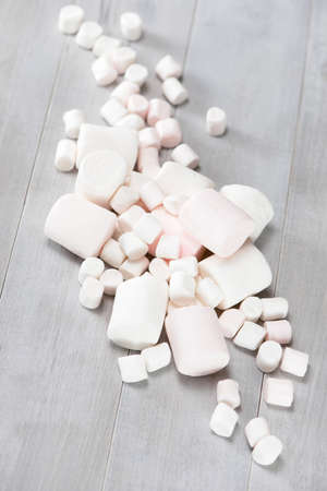 Various white marshmallows on the grey wooden table Imagens
