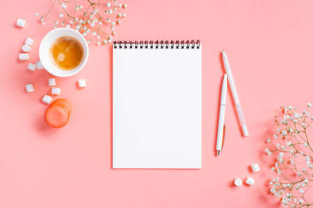 Tender light pink background with opened notepad and cup of coffee, copy space Imagens