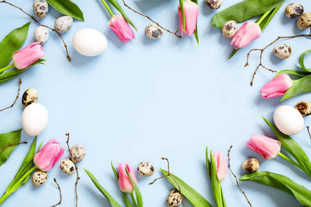 Blue background decorated with chicken and quail easter eggs, pink tulips and branches, copy space