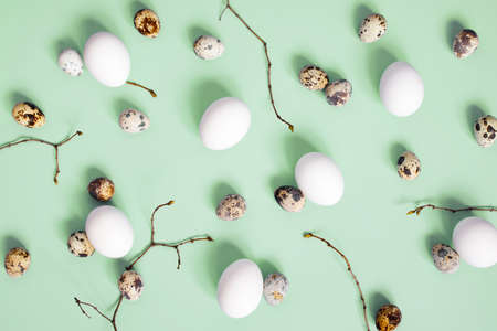 Pattern of chicken and quail easter eggs and branches on the green background, top view