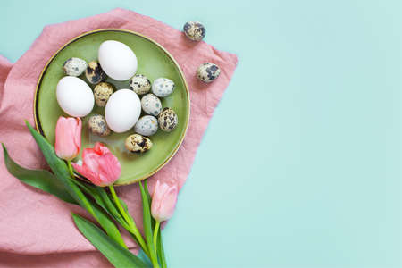 Background with chicken and quail eggs on the green plate and tulips, pink linen tablecloth, top view