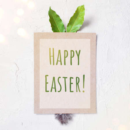 The blank poster with bunny ears and tail with text Happy Easter on the white textured table, copy space Imagens
