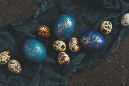 Background with painted blue Easter eggs with golden spots, copy space