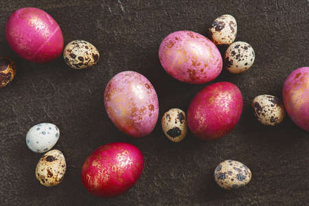 Pattern of painted colorful Easter eggs with golden spots, top view