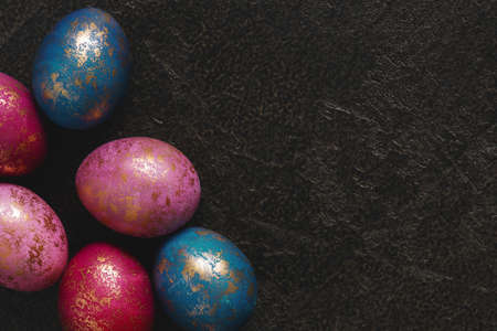 Background with painted colorful Easter eggs with golden spots, copy space Imagens
