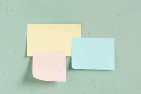 Three various paper sticks on the green textured wall, copy space