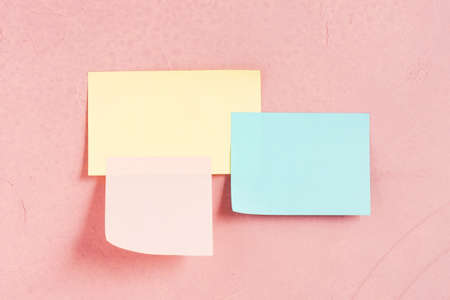 Three various paper sticks on the pink-coral textured wall, copy space