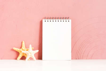 Blank white notepad and starfishes on the wooden table against the pink-coral textured wall, copy space