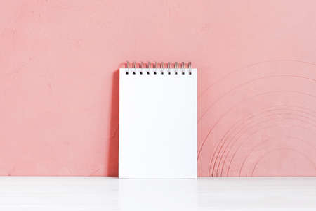 Blank white notepad on the wooden table against the pink-coral textured wall, copy space