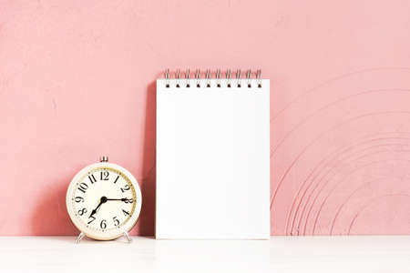 Alarm clock and blank notepad on the wooden white table against the pink-coral textured wall, copy space