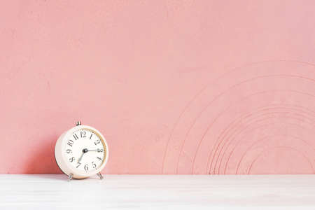 Alarm clock on the wooden white table against the pink-coral textured wall, copy space Imagens