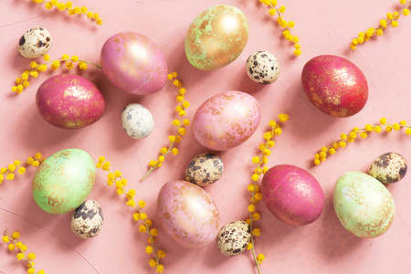Pattern with pink Easter eggs with golden spots and flowers on the pink table, copy space Imagens
