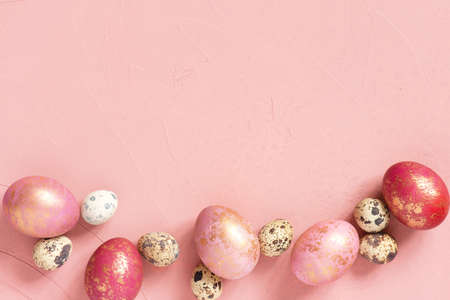 Background with various Easter eggs with golden spots on the pink table, copy space