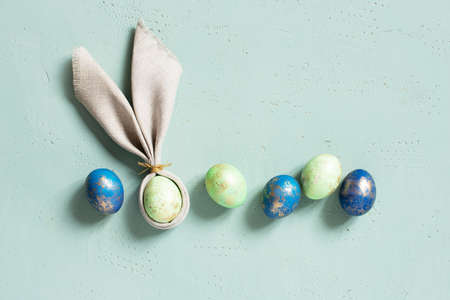 Easter eggs with golden spots, bunny ears of linen napkin on the blue textured table, top view