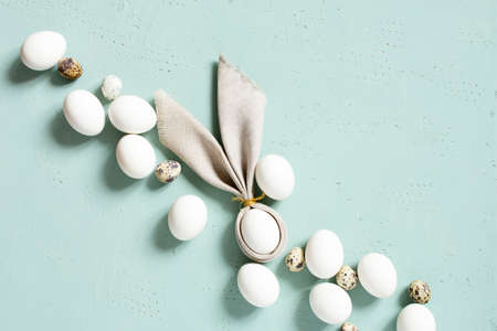 Chicken and quail eggs with bunny ears of linen napkin on the blue textured table, Easter composition, top view