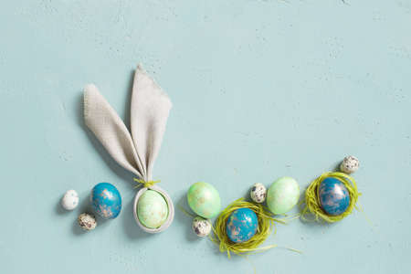 Background with Easter eggs with golden spots, bunny ears of linen napkin on the blue textured table, top view